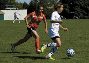 Shelly Bateman carries the ball away from Cobleskill midfielder Katelyn Benjamin