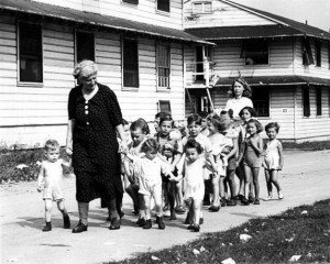 A woman leads a group of children through the camp