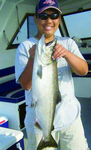 James Seegars, member of the Fishing Club shows off a 13 pound fresh king salmon he caught. (Photo provided by Fishing Club)