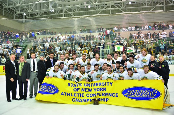 The Oswego State men's hockey team poses with the SUNYAC championship trophy and banner after defeating SUNY Plattsburgh 4-0 on Saturday night. (Nick Graziano | The Oswegonian)