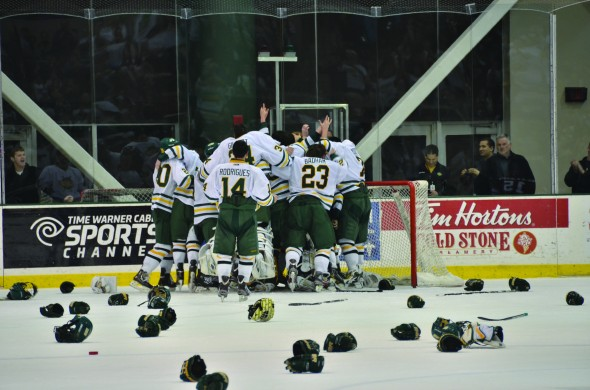 The Oswego State men's hockey team celebrates on the ice after defeating SUNY Plattsburgh on Saturday. (Nick Graziano | The Oswegonian)
