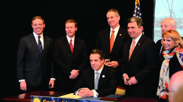 Gov. Andrew Cuomo (sitting) came to Oswego State on April 3 to sign the third consecutive on-time budget of his tenure as governor of New York. (Patrick Malowski | The Oswegonian)