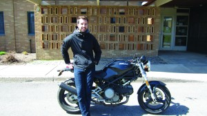 Ted Winkworth with the motorcycle he will use on his trip across North America and South America. (Justine Polonski | The Oswegonian)
