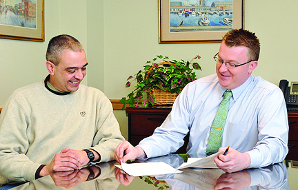 Milton Lopez, a former Army National Guard member and veteran of Afghanistan, is seen here working with Ben Parker, an employee for the Division of Extended Learning, as they plan Lopez's education. (Photo provided by Public Affairs)