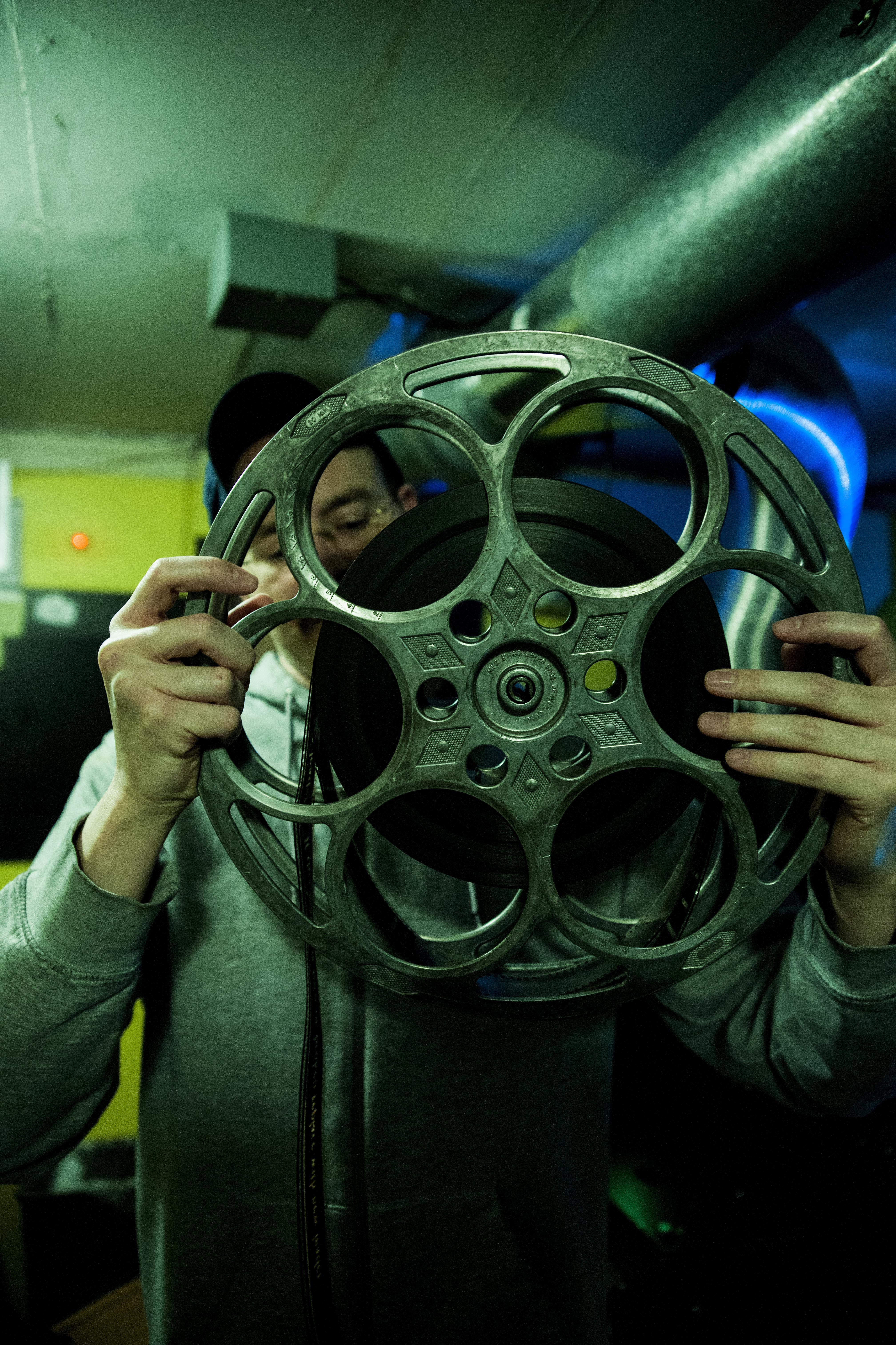 John Nagelschmidt Jr. holding one of the film reels that would have been used with their old projection system.