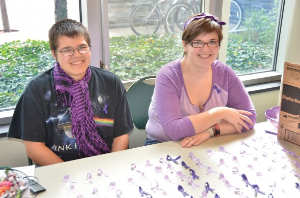 Devon Perkins and Marian Holmes, members of Pride Alliance giving out Spirit Day ribbons in Campus Center.  (Moraima Capellán Pichardo | The Oswegonian)