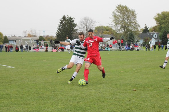 Junior Jim Manton fights for the ball with a Cortland player in Oswego State's 5-0 loss to the Red Dragons.  (Perry Kennedy | The Oswegonian)