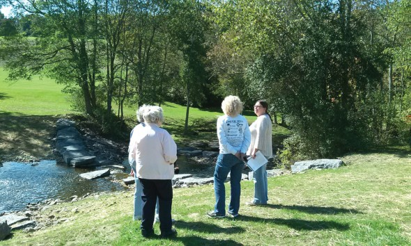 Participants of the nature walk discuss the Fallbrook Dam project. The walk was hosted by Rice Creek Field Station.   (Jihyoung Son | The Oswegonian)