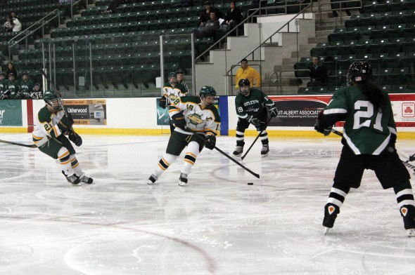 Senior captain Olivia Boersen (18) takes the puck through the Castleton zone during the Lakers' 3-2 win.  (Perry Kennedy   The Oswegonian)