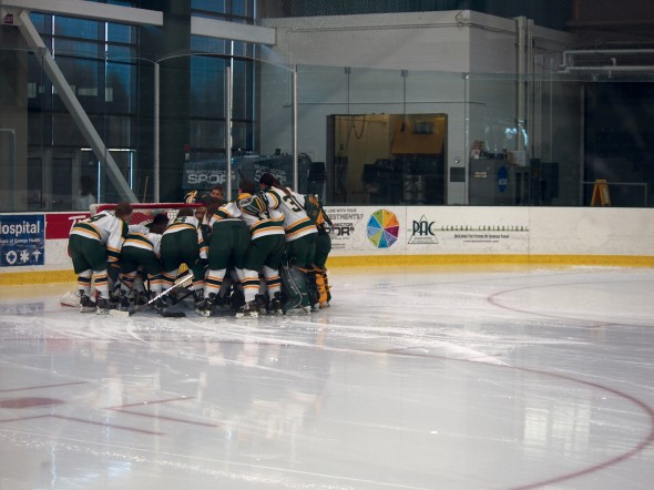 The Oswego State women's hockey team gathers around the net before a home game against conference rival Neumann. The Lakers swept the weekend series.  (Nicole Sussman | The Oswegonian)