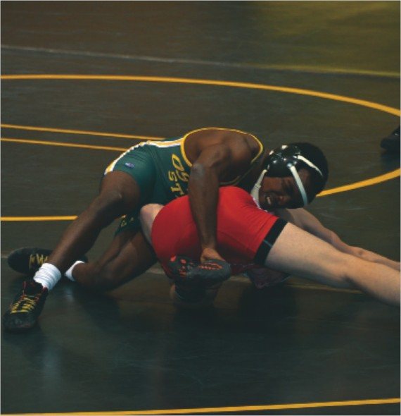 Junior Quamaine Thomas tries to pin down his Red Dragon opponent. Thomas earned a 6-4 win less than a minute into overtime.  (Seamus Lyman | The Oswegonian)