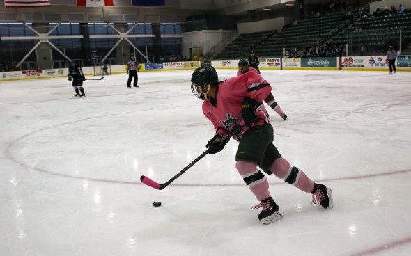 "Erika Truschke takes the puck along the boards, sporting a pink jersey for the ""Pink the Rink"" weekend.  (Perry Kennedy 