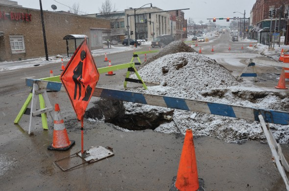 The hole in the ground where the water main break occurred at the corner of Water Street and Bridge Street.   (Connor Gannon | The Oswegonian)