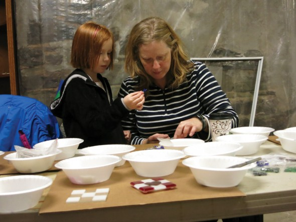 Two participants in the event at Lakeside Artisans sort through glass pieces to find the right pick for their valentine before it is baked in a kiln and becomes a finished product.  (Chloé Larson | The Oswegonian)