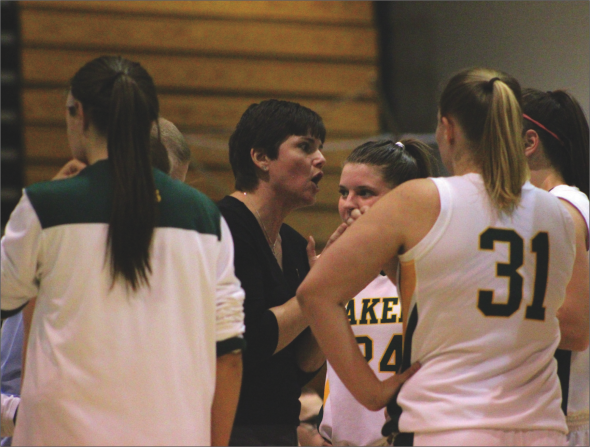 Tracy Bruno (center) talks to her players in a team huddle during the Lakers' game against SUNY Cortland.  (David Armelino | The Oswegonian)