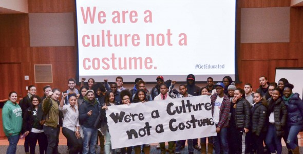 Students attending the BSU meeting March 10 pose with a sign protesting against insensitive costumes.  (Moraima Capellán Pichardo | The Oswegonian)