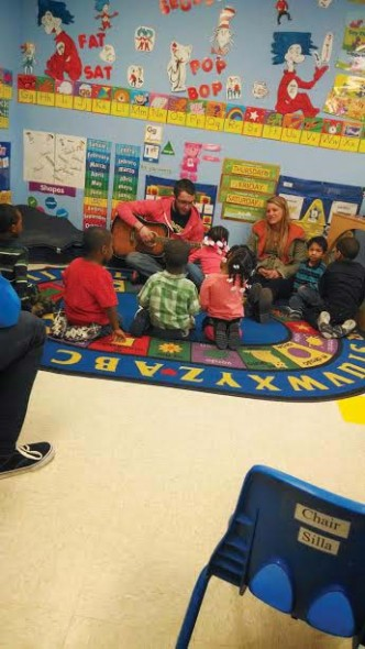 Kyle Decarr (center) plays a guitar for a group of children on his visit to New Jersey for Alternative Spring Break.  (Photo provided by Kendra Bowman)