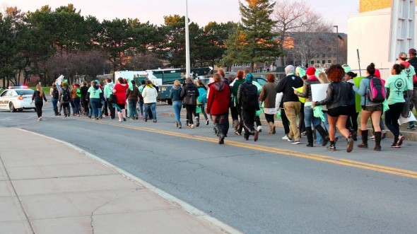 Students walk around Oswego State  on the march portion of Slut Walk behind a University Police car to help raise awareness for  rape prevention.  (David Armelino | The Oswegonian)