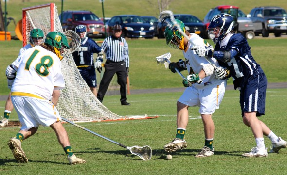 Sophomore defender Luke Bender (left) attempts to scoop up the ball near the net during Oswego State's 21-6 Senior Day win against SUNY Canton.  (Maximilian E. Principe | The Oswegonian)