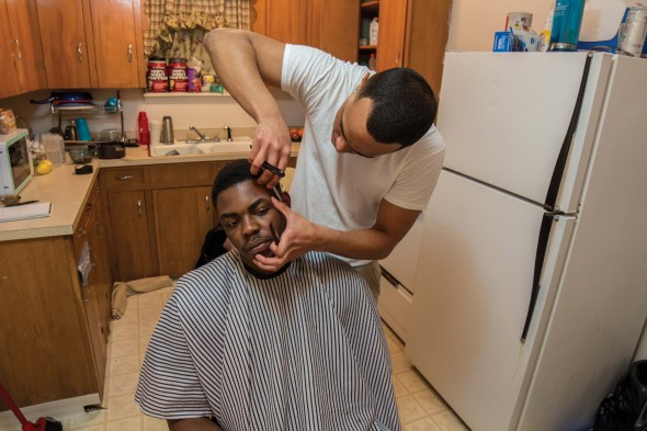 Sean Ebanks cuts fellow Oswego State student Sunday Bamgbose's hair in his Oswego apartment.  (Moraima Capellán Pichardo | The Oswegonian)