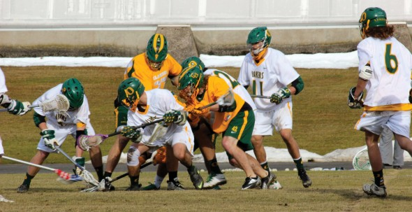 Members of the Oswego State men's lacrosse team (white) fight for possession of the ball in the Lakers' 11-9 loss against Clarkson University on April 1.  (Maximilian E. Principe | The Oswegonian)