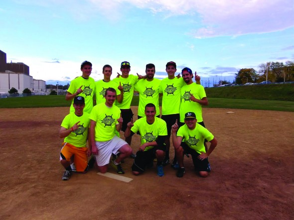 Members of Sons of Pitches pose on the mound of West Lee Field in their championship shirts after Tuesday's men's competitive softball league finals victory.  (Photo Provided by Campus Recreation)