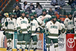 Members of Oswego State wait along the boards as the officials and captains discuss  whether or not sophomore Mitch Herlihey's third period shot did or did not cross the goal line. If counted, the goal would have given the Lakers a 5-4 lead (David Armelino | The Oswegonian).