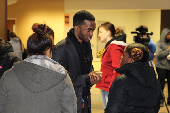 Christopher Collins-McNeil (center) speaks with students at a protest inside the Marano Campus Center. (Seamus Lyman | The Oswegonian)