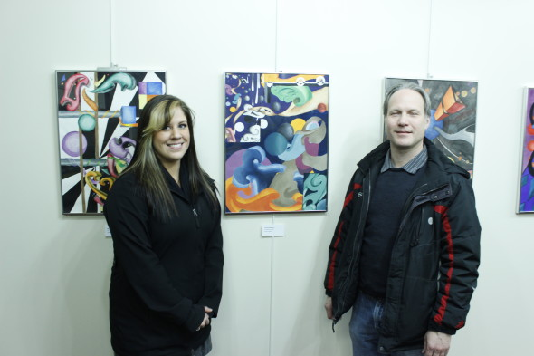Vanessa Minges (left) and Professor Rick Metzgar (right) at the student art exhibition. (Alexander Simone | The Oswegonian)