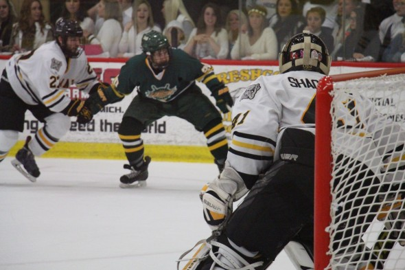 Adrian College goalie Scott Shackell (41) follows Oswego State's offensive play as senior Laker Mike Montagna chases down the puck. Shackell finished with 31 saves in the Bulldogs' 5-4 victory in the NCAA Quarterfinals in Adrian, Mich. (Seamus Lyman | The Oswegonian)
