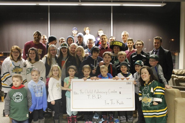 Members of Delta Kappa Kappa and the men's ice hockey team pose with children during an ice hockey game. (Photo provided by Denvol Haye)