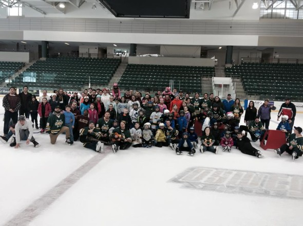 Participants of the For the Kids free skate pose for a photo at center ice in the Marano Campus Center ice arena. (Photo provided by Denvol Haye)