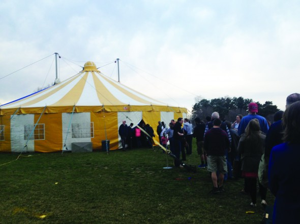 Audience members enter the sold out Vague de Cirque's striped yellow tent outside Marano Campus Center. (Lydia Goerner | The Oswegonian)